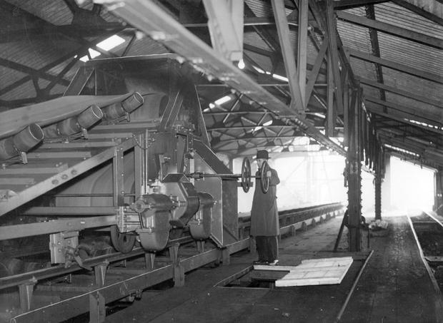 On a visit to the Gasworks an employee demonstrates the Coal Gripper (The feed system of a coal getting combine, which works with a face conveyor, comprises: a traction device located on the combine and having a cylinder-shaped sprocket on the side surface of which a circular spherical-shaped recess is provided, slots being made on both inner sides of the spherical recess, said slots having an involute-spherical surface)   20/1/1938
