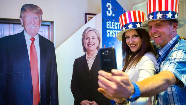 People in patriotic top hats take photographs next to cardboard figures depicting Donald Trump the Republican, left, and Hillary Clinton, the Democratic presidential candidates, during the Election Night Party at the US Embassy in Budapest, Hungary, Tuesday, Nov. 8, 2016. (Balazs Mohai/MTI via AP)