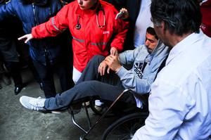 Kneesy does it: Luis Suarez is wheeled out of hospital after the surgery which rules him out of facing Northern Ireland