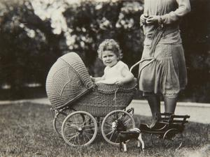 Previously unpublished family photograph issued by the Royal Collection of Queen Elizabeth II sitting in a wicker pram in 1928. The pictures are to be seen by the public for the first time to coincide with a book being released this week to mark the birth of Prince George contains new pictures which show the future Queen between the ages of two and four