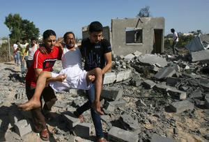 Palestinians help a man wounded as they walk over the rubble of destroyed buildings following an Israeli airstrike in Khan Younis in the southern Gaza Strip, Wednesday, July 30, 2014. (AP Photo/Eyad Baba)