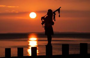 Piper Louise Marshall plays at dawn along Edinburgh's Portobello Beach overlooking the Firth of Forth on the 75th anniversary of VE Day. PA Photo. Picture date: Friday May 8, 2020. See PA story MEMORIAL VE. Photo credit should read: Jane Barlow/PA Wire