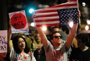 A man holds an American flag upside down as he stands with others on Broadway, Wednesday, Nov. 9, 2016, in downtown San Diego, during a protest in opposition of Donald Trump's presidential election victory. (Hayne Palmour IV/The San Diego Union-Tribune via AP)
