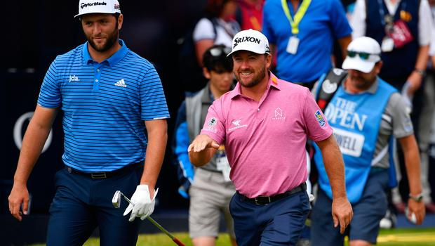 Spain's Jon Rahm (L) and Northern Ireland's Graeme McDowell walk along the fairway at the first hole during a practice session at The 148th Open golf Championship at Royal Portrush golf club in Northern Ireland on July 16, 2019. (Photo by Paul ELLIS / AFP) / RESTRICTED TO EDITORIAL USEPAUL ELLIS/AFP/Getty Images
