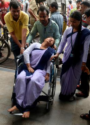 Indian hospital staff attend to a schoolgirl who fainted as a tremor struck at Siliguri Hospital in Siliguri on May 12, 2015.   A new earthquake of 7.3-magnitude and several powerful aftershocks hit devastated Nepal on May 12, killing at least four people and sending terrified residents running into the streets of the traumatised capital. The quake was felt as far away as New Delhi, and officials said it caused buildings to collapse in Chinese-controlled Tibet.  AFP PHOTO/Diptendu DUTTADIPTENDU DUTTA/AFP/Getty Images