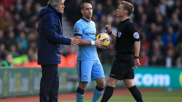 Match referee Mike Jones has a word with Manchester City manager Manuel Pellegrini during the Barclays Premier League match at St Mary's Stadium, Southampton. Nick Potts/PA Wire.