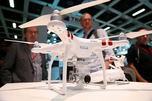 BERLIN, GERMANY - SEPTEMBER 03: Visitors look at a Phantom 3 Standard quadcopter drone at the DJI stand during a press day at the 2015 IFA consumer electronics and appliances trade fair on September 3, 2015 in Berlin, Germany. The 2015 IFA will be open to the public from September 4-9.    (Photo by Sean Gallup/Getty Images)