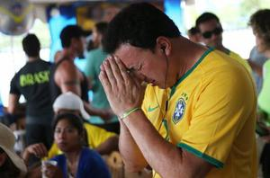 A Brazilian fan prays before the semifinal World Cup game against Germany on July 8, 2014 in Port Chester, United States. Fans, mostly for Brazil, gathered at the Copacabana Restaurant in Westchester County to watch on outdoor TV screens.  (Photo by John Moore/Getty Images)