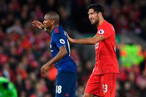 Liverpool's German midfielder Emre Can (R) gives Manchester United's English midfielder Ashley Young a helping push as he's substituted during the English Premier League football match between Liverpool and Manchester United at Anfield in Liverpool, north west England on October 17, 2016. AFP/Getty Images