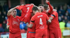 Larne players pay tribute to Jerry Thompson after their opening goal at Inver Park.