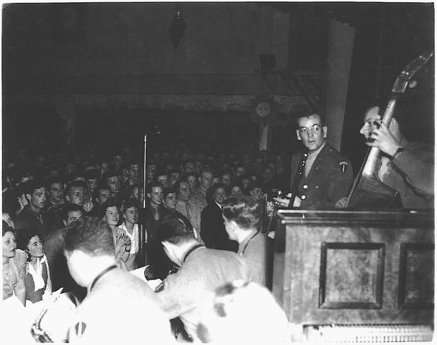 The legendary Glenn Miller and his orchestra playing to a devoted audience at a wartime gig.