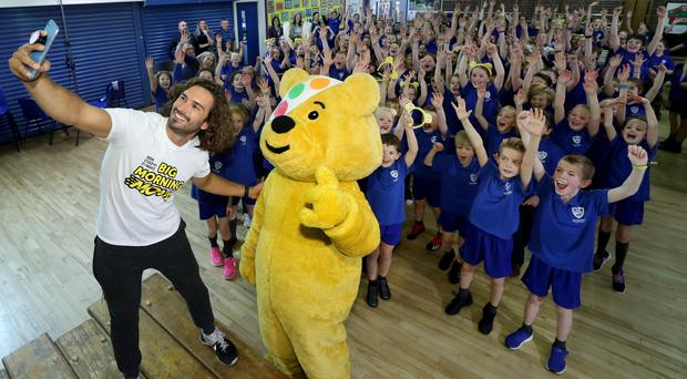 Fitness expert Joe Wicks with Pudsey and pupils from Academy Primary School