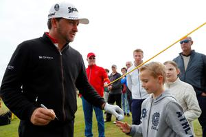 Sign here: Graeme McDowell autographs a ball for a young fan at Royal Troon