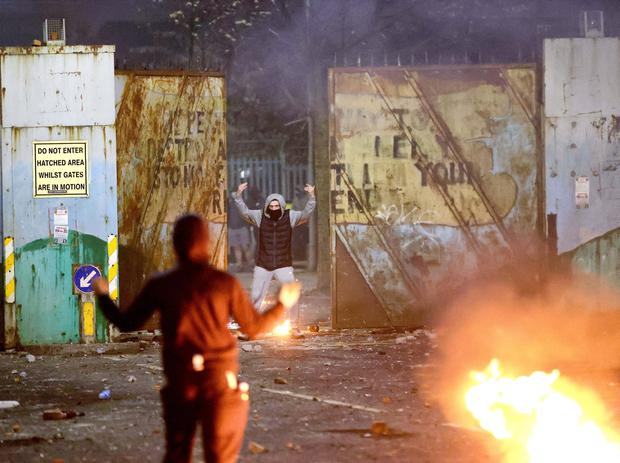 A Loyalist and Nationalist rioter confront each other at Lanark Way interface in Belfast on Wednesday night. Loyalists had blocked traffic during a protest which then erupted into a riot. Pic Pacemaker
