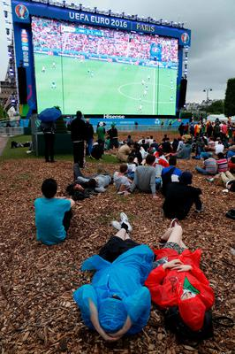 People in plastic rain ponchos lie on the ground as they watch the Euro 2016 group C football match between Northern Ireland and Germany at the fan zone near the Eiffel Tower in Paris on June 21, 2016.   / AFP PHOTO / THOMAS SAMSONTHOMAS SAMSON/AFP/Getty Images
