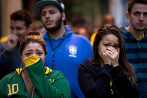 Brazil soccer fans watch their team lose to Germany in a World Cup semifinal game on TV in Sao Paulo, Brazil, Tuesday, July 8, 2014. (AP Photo/Rodrigo Abd)