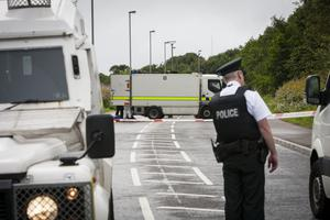 A police officer keeps an eye on proceedings during a security alert at Southway, Derry. Southway is an arterial route into the Creggan Estate in the city. The area was still sealed off at 4.30pm.