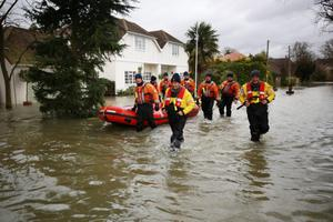 A fire and rescue team make their way through flood water on February 12, 2014 in Wraysbury, England. The Environment Agency contiues to issue severe flood warnings for a number of areas on the river Thames in the commuter belt west of London. With heavier rains forecast for the coming week people are preparing for the water levels to rise.  (Photo by Peter Macdiarmid/Getty Images)