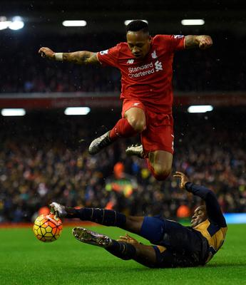 Liverpool's English defender Nathaniel Clyne (top) is tackled by Arsenal's Costa Rican striker Joel Campbell during the English Premier League football match between Liverpool and Arsenal at Anfield stadium in Liverpool, north-west England on January 13, 2016. AFP PHOTO / PAUL ELLIS RESTRICTED TO EDITORIAL USE. NO USE WITH UNAUTHORIZED AUDIO, VIDEO, DATA, FIXTURE LISTS, CLUB/LEAGUE LOGOS OR 'LIVE' SERVICES. ONLINE IN-MATCH USE LIMITED TO 75 IMAGES, NO VIDEO EMULATION. NO USE IN BETTING, GAMES OR SINGLE CLUB/LEAGUE/PLAYER PUBLICATIONS.PAUL ELLIS/AFP/Getty Images