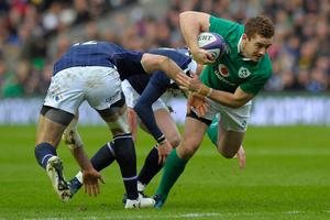 Ireland's fly-half Paddy Jackson (R) breaks a tackle during the Six Nations international rugby union match between Scotland and Ireland at Murrayfield in Edinburgh, Scotland on Febuary 4, 2017.   / AFP PHOTO / Andy BuchananANDY BUCHANAN/AFP/Getty Images