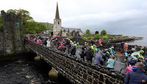 The peloton passes through Glenarm village during stage two of the 2014 Giro D'Italia in Co Antrim. PRESS ASSOCIATION Photo. Picture date: Saturday May 10, 2014. Photo credit should read: Paul Faith/PA Wire
