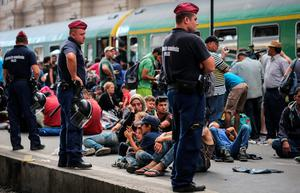 BUDAPEST, HUNGARY - SEPTEMBER 03:  Police stand guard as migrants sit on the platform of Keleti station after it was reopened this morning in central Budapest on September 3, 2015 in Budapest, Hungary. Although the station has reopened all international trains to Western Europe have bee cancelled. According to the Hungarian authorities a record number of migrants from many parts of the Middle East, Africa and Asia are crossing the border from Serbia. Since the beginning of 2015 the number of migrants using the so-called Balkans route has exploded with migrants arriving in Greece from Turkey and then travelling on through Macedonia and Serbia before entering the EU via Hungary. The massive increase, said to be the largest migration of people since World War II, led Hungarian Prime Minister Victor Orban to order Hungary's army to build a steel and barbed wire security barrier along its entire border with Serbia, after more than 100,000 asylum seekers from a variety of countries and war zones entered the country so far this year.  (Photo by Matt Cardy/Getty Images)