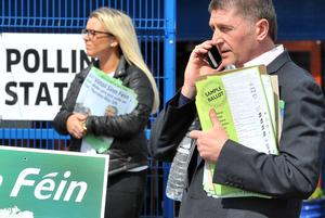 Sinn Fein supporters holding sample ballot sheets, showing people how to vote, outside St Teresa's Polling Station in West Belfast