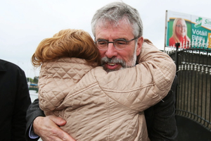 Sinn Fein Leader Gerry Adams receives a hug from a well wisher outside Sinn Fein offices on the Falls Road, Belfast