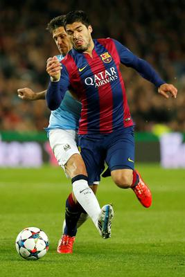 Manchester City's Martin Demichelis, left, tackles Barcelona's Luis Suarez to receive a yellow card during a Champions League round of 16 second leg, soccer match between FC Barcelona and Manchester City at Camp Nou stadium, in Barcelona, Spain, Wednesday, March 18, 2015. (AP Photo/Emilio Morenatti)