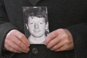 Patrick McElhone's brother Mickey with a photograph of his brother Patrick outside Omagh Court House on Thursday. Picture Martin McKeown. 21.01.21