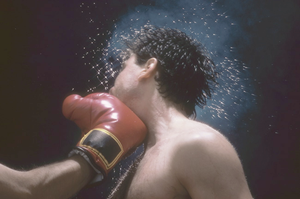 Sweat flying from boxer's head from force of punch