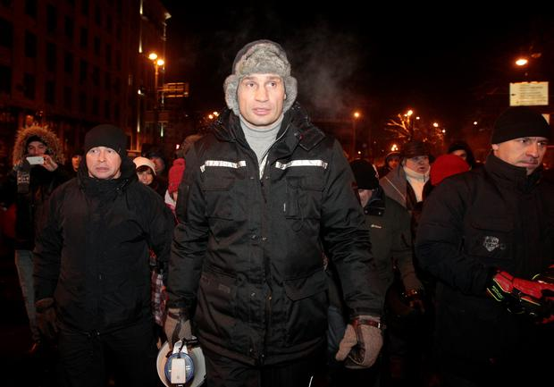 Opposition leader and former WBC heavyweight boxing champion Vitali Klitschko, center, addresses protesters near barricades between police and protesters in central Kiev, Ukraine, Thursday Jan. 23, 2014. Emerging from hours-long talks with President Viktor Yanukovych, opposition leader Oleh Tyahnybok asked demonstrators in Kiev for several more days of a truce, saying the president has agreed to ensure the release of dozens of detained protesters and stop further detentions. But other opposition leaders offered mixed reports on the outcome of the meeting, with Vitali Klitschko saying negotiations had brought little result. (AP Photo/Sergei Chuzavkov)