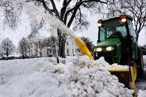 Snow arcs in the air as it is removed from the driveway at the White House in Washington, Thursday, Feb. 13, 2014. After pummeling wide swaths of the South, a winter storm dumped nearly a foot of snow in Washington as it marched Northeast and threatened more power outages, traffic headaches and widespread closures for millions of residents. (AP Photo/Jacquelyn Martin)