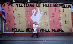 LIVERPOOL, ENGLAND - APRIL 15:  A woman walks past a Hillsborough tribute banner as fans arrive in Anfield for a memorial service marking the 25th anniversary of the Hillsborough Disaster at Anfield stadium on April 15, 2014 in Liverpool, England. Thousands of fans, friends and relatives are attending the service at Liverpool's Anfield stadium to mark the 25th anniversary of the Hillsborough disaster. Bells across the City of Liverpool will ring during a one minute silence. A total of 96 Liverpool supporters lost their lives during a crush at an FA Cup semi final against Nottingham Forest at the Hillsborough football ground in Sheffield, South Yorkshire in 1989.  (Photo by Christopher Furlong/Getty Images)