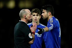 Referee Mike Dean (L) talks with Chelsea's Brazilian-born Spanish striker Diego Costa (R) after Costa was penalised for an off-the-ball incident during the English Premier League football match between Watford and Chelsea at Vicarage Road Stadium in Watford, north of London on February 3, 2016. / AFP / ADRIAN DENNIS / RESTRICTED TO EDITORIAL USE. No use with unauthorized audio, video, data, fixture lists, club/league logos or 'live' services. Online in-match use limited to 75 images, no video emulation. No use in betting, games or single club/league/player publications.  / ADRIAN DENNIS/AFP/Getty Images
