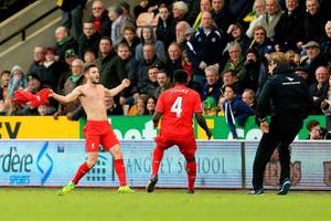 Adam Lallana (L) of Liverpool ceelbrates scoring his team's fifth goal with his manager Jurgen Klopp (R) and team mate Kolo Toure (C) during the Barclays Premier League match between Norwich City and Liverpool at Carrow Road on January 23, 2016 in Norwich, England.  (Photo by Stephen Pond/Getty Images)