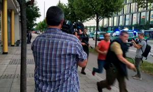 Armed police move past onlooking media responding to a shooting at a shopping center in Munich, Germany, Friday July 22, 2016. (AP Photo/APTV)