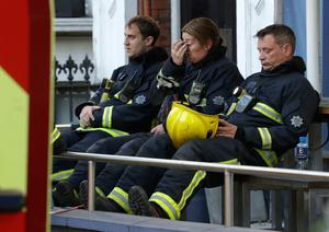 Firefighters wait to start their shift after a massive fire raged in a 27-floor high-rise apartment building in London, Wednesday, June 14, 2017. (AP Photo/Matt Dunham)