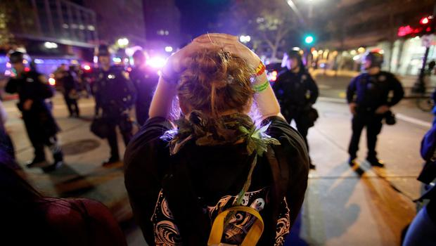 A protester faces a police line in downtown Oakland, Calif., early Wednesday, Nov. 9, 2016. President-elect Donald TrumpÄôs victory set off multiple protests. (Jane Tyska/Bay Area News Group via AP)