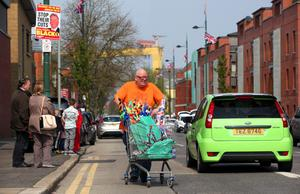 The Annual Easter Apprentice Boys' Parade made its way from Belmont Road where an act of Remembrance took place to Ormeau Embankment. A man selling flags from a trolley makes his way up Templemore Avenue.