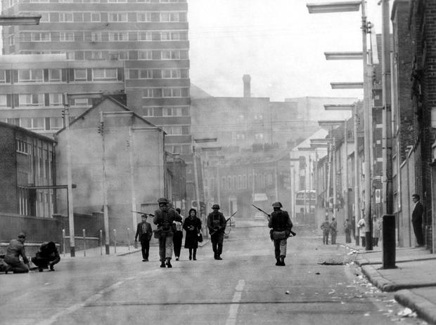 RIOTS. BELFAST. AUGUST 1969. A family leaving the sealed-off area, are escorted down Divis Street by troops.