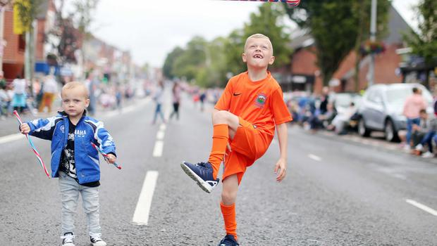 Press Eye - Belfast -  Northern Ireland - 13th July  2015  Belfast's Orange Order annual 12th of July demonstration makes its way through the City Centre to the field at Malone House beside Shaws Bridge.  Left to right.  Zac Jamison(3) and Marcus Toan(7) wait for the parade on the Lisburn Road.   Picture by Jonathan Porter/Press Eye