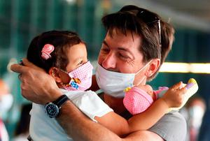 Happy reunion: a father returning from work abroad is reunited with his daughter at the airport