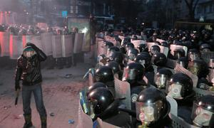 A protester stands in front of riot police in central Kiev, Ukraine, Sunday, Jan. 19, 2014. Hundreds of protesters on Sunday clashed with riot police in the center of the Ukrainian capital, after the passage of harsh anti-protest legislation last week seen as part of attempts to quash anti-government demonstrations. A group of radical activists began attacking riot police with sticks, trying to push their way toward the Ukrainian parliament building, which has been cordoned off by rows of police and buses. (AP Photo/Efrem Lukatsky)