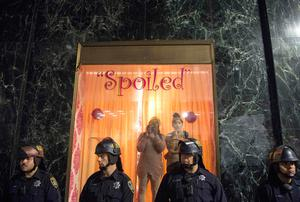Police guard a shop as two women look out during an anti-Trump protest in Oakland, California on November 9, 2016.  Thousands of protesters rallied across the United States expressing shock and anger over Donald Trump's election, vowing to oppose divisive views they say helped the Republican billionaire win the presidency. / AFP PHOTO / Josh EdelsonJOSH EDELSON/AFP/Getty Images