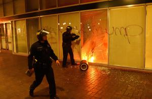 Police investigate a fire lit by protesters inside a building during an anti-Trump protest in Oakland, California on November 9, 2016.  Thousands of protesters rallied across the United States expressing shock and anger over Donald Trump's election, vowing to oppose divisive views they say helped the Republican billionaire win the presidency. / AFP PHOTO / Josh EdelsonJOSH EDELSON/AFP/Getty Images