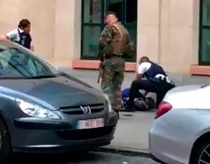 Police officials and a soldier looking at a man on the pavement in the city centre of Brussels after man alleged to have attacked soldiers with a knife and was shot.  / AFP PHOTO / Belga / STR / Belgium OUTSTR/AFP/Getty Images