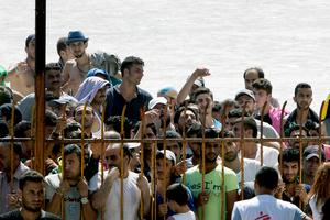 "Migrants wait behind a fence outside a stadium in order to be registered by the police on the Greek island of Kos on August 12, 2015. The number of migrants and refugees arriving on Greece's shores has exploded this year, but the Mediterranean country provides virtually no reception facilities and leaves them wallowing in ""totally shameful"" conditions, a UN official said on August 7. The UN refugee agency's division for Europe said 124,000 refugees and migrants have landed in Greece since the beginning of the year. AFP PHOTO / ANGELOS TZORTZINISANGELOS TZORTZINIS/AFP/Getty Images"