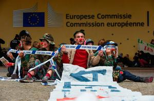 """People dressed like clowns sit on the ground and hold ribbons reading """"Transatlantic Trade and Investment Partnership (TTIP) free-zone"""" during a protest against the EU-Canada Comprehensive Economic and Trade Agreement (CETA) at European Union Commission headquarters in Brussels on October 27, 2016. Belgium announced on October 27, 2016 a breakthrough in talks to secure a landmark EU-Canada trade deal by winning over the leaders of a recalcitrant Belgian region, potentially snapping a deadlock which threatened European credibility anew. However, the announcement came too late for EU leaders and Canadian Prime Minister Justin Trudeau to go ahead with a signing ceremony in Brussels on October 27, 2016.  / AFP PHOTO / JOHN THYSJOHN THYS/AFP/Getty Images"""