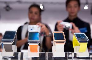 People take photos of new Samsung Galaxy Gear after the presentation in Berlin, Germany, Wednesday, Sept. 4, 2013. Samsung has unveiled a highly anticipated digital wristwatch well ahead of a similar product expected from rival Apple. The so-called smartwatch is what some technology analysts believe could become this year's must-have holiday gift. Samsung unveiled the Galaxy Gear on Wednesday in Berlin ahead of the annual IFA consumer electronics show. (AP Photo/Gero Breloer)